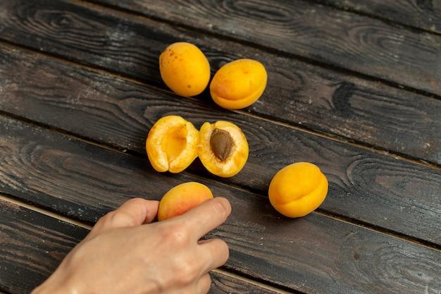茶色の素朴な背景の新鮮なスナックの平面図甘い黄色いアプリコットまろやかで新鮮な果物
