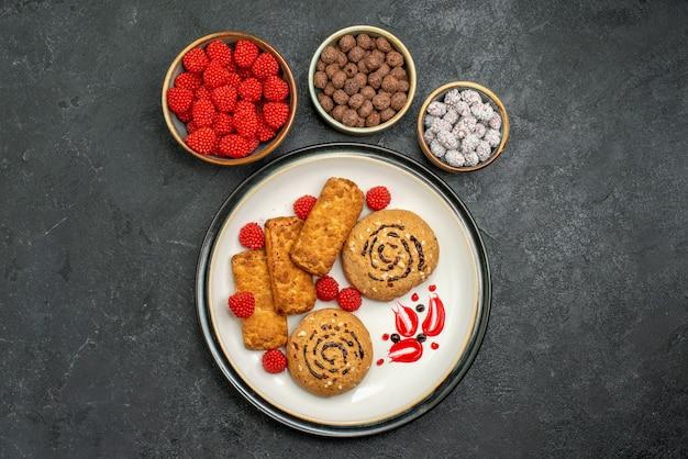 灰色の背景にキャンディーと甘いおいしいクッキーの上面図シュガークッキー甘いキャンディーケーキ
