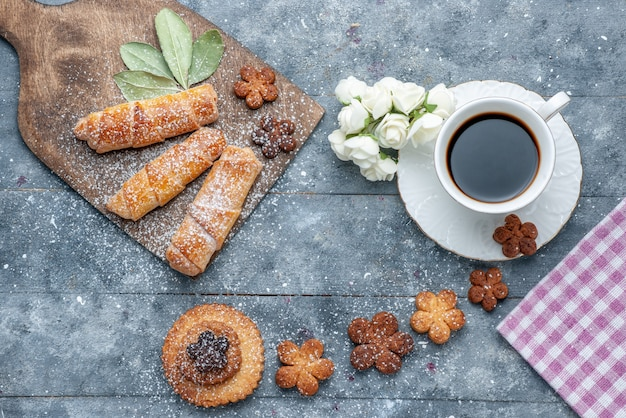 Top view sweet yummy cookies with cup of coffee and sweet bangles the grey background cookie sugar sweet coffee