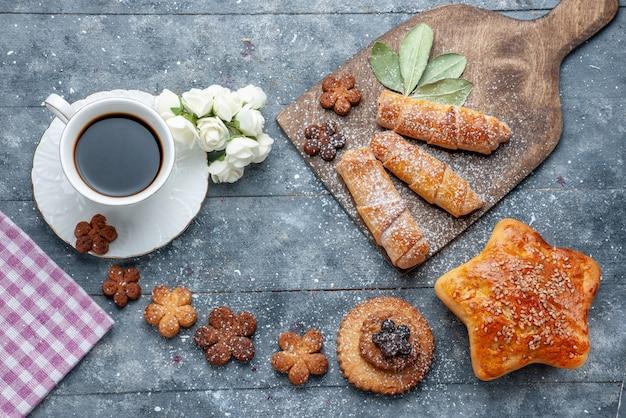 Vista dall'alto dolci deliziosi biscotti con una tazza di caffè e braccialetti dolci il caffè dolce zucchero grigio da scrivania