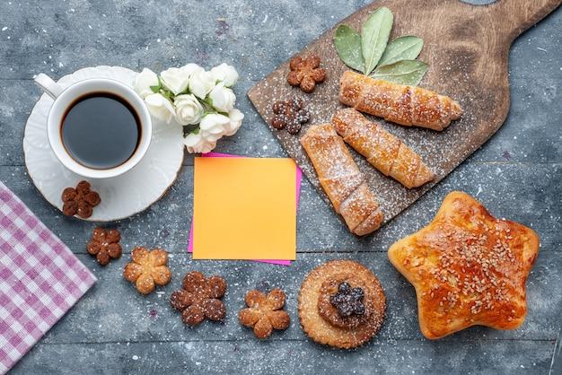 トップビュー一杯のコーヒーとペストリーの甘いおいしいクッキーと灰色のテーブルクッキーシュガースイートコーヒー