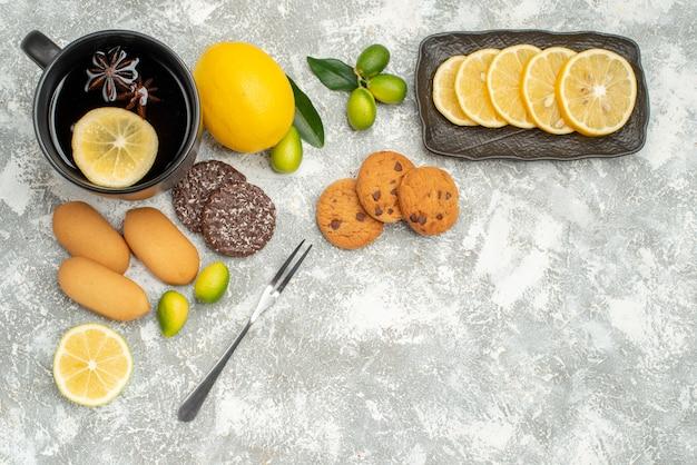 Вид сверху сладости чашка чая с лимонным печеньем цитрусовые нарезанные вилкой лимона
