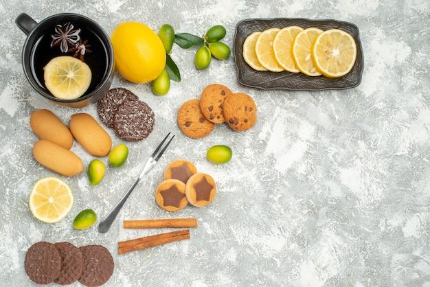 Вид сверху сладости чашка чая с звездчатым анисом цитрусовые нарезанные лимонной вилкой аппетитное печенье