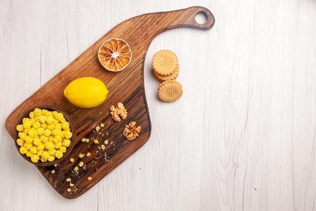 白いテーブルの左側にあるクッキーの横にあるまな板の上のビューのお菓子とキャンディーボウルキャンディーナッツとレモン