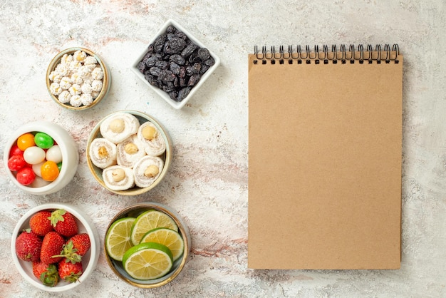 Vista dall'alto dolci in ciotole per quaderni con crema ciotole di fragole e dolci sul tavolo bianco
