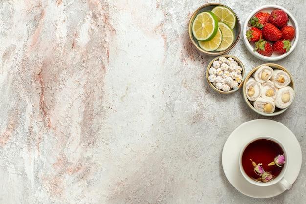 Vista dall'alto dolci in ciotole una tazza di tè sul piattino bianco accanto alle ciotole di appetitosi frutti di bosco e dolci sul tavolo bianco