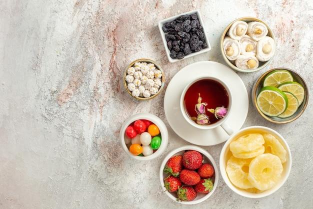 Vista dall'alto dolci in ciotole fette di ananas essiccato lime e dolci accanto alla tazza di tè nero sul piattino sul lato destro del tavolo