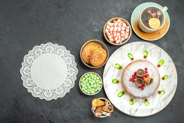 Vista dall'alto della torta di dolci con bacche di pizzo centrino verde dolci cialde una tazza di tè