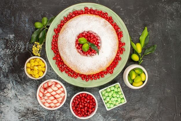 Torta di dolci vista dall'alto con melograno tre ciotole di lime dolci semi di melograno