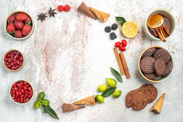 Vista dall'alto dolci una tazza di tè con biscotti al cioccolato alla cannella ciotole di marmellata di frutti di bosco agrumi