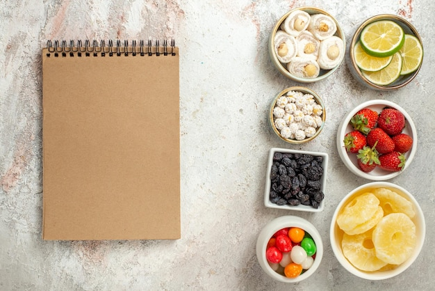 흰색 탁자에 있는 라임 딸기 과자와 말린 파인애플 그릇 옆에 있는 그릇 크림 공책의 상위 뷰 과자
