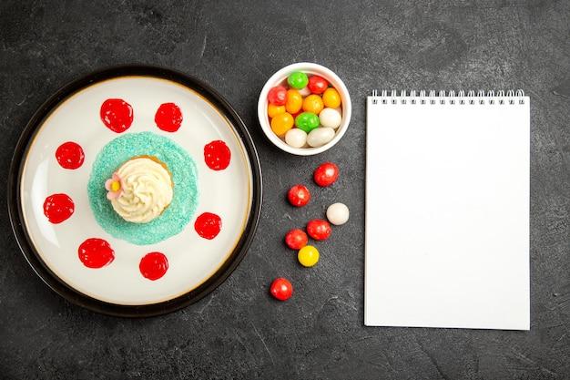 Вид сверху сладости на столе, аппетитный кекс рядом с миской конфет и белый блокнот на черном столе