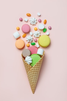 Top view of sweets spilling out of waffle cone on pastel pink background