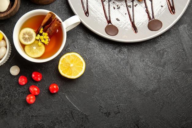 Vista dall'alto dolci e tè bianco tazza di tè con bastoncini di cannella e piatto di torta al limone e ciotole di cioccolato e caramelle sul tavolo scuro