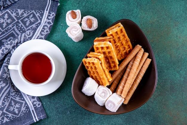 Dolci di vista superiore waffles panini dolci e marmellata con una tazza di tè sul verde
