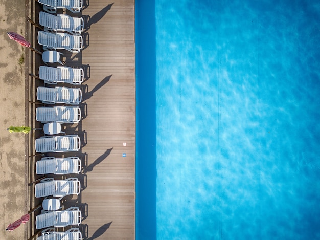 Top view of a swimming pool with white sun beds in a row