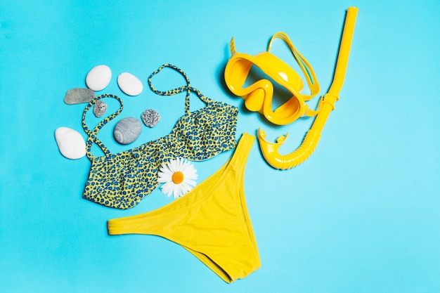 Top view of swimsuit and diving mask near chamomile flower and pebbles  background.