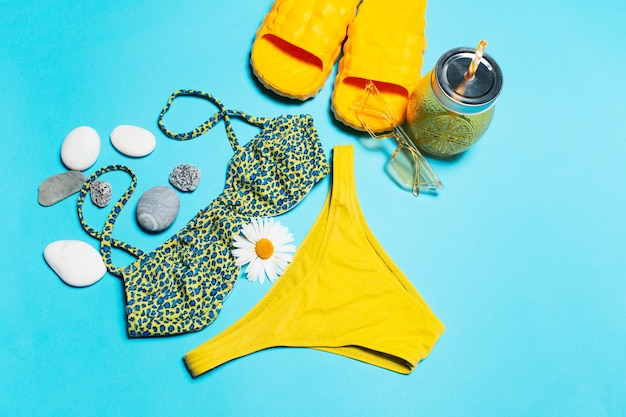 Top view of swimsuit, sunglasses, slippers and juice glass mug decorated with pebbles and chamomile