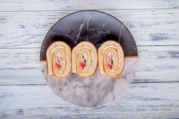 Top view of swiss roll slices with whipped cream and raspberry jam on a plate on rustic background