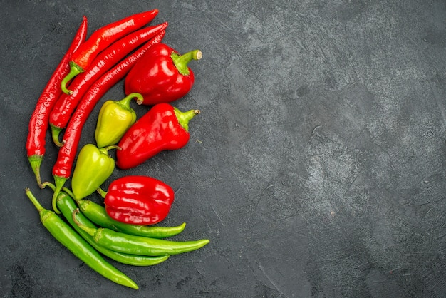 Top-view symmetric framed peppers with its bright colors on dark surface with free space
