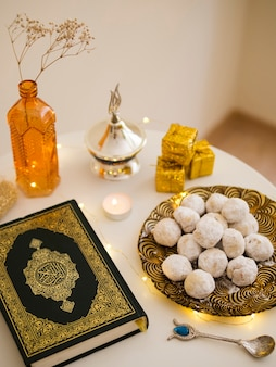 Top view table arrangement with quran, pastries and tea