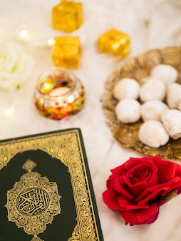 Top view table arrangement with quran, roses and pastries