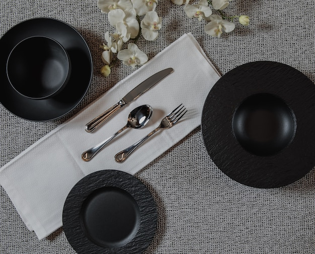 Top view of table setting on gey surface with empty black plates and silver spoon fork and knife