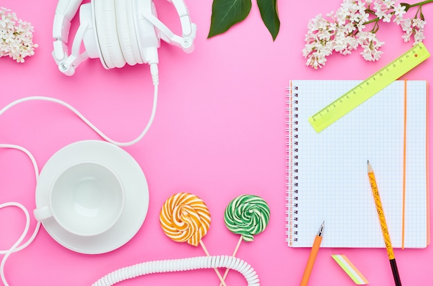 Top view of the table of a teenage child, composition of pencil for laptop eraser flower glass with drink earphone lollipop on pink background