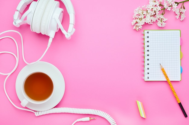 Top view of the table of a teenage child, the composition of the pencil notebook eraser flower drink glass with headphones on pink background