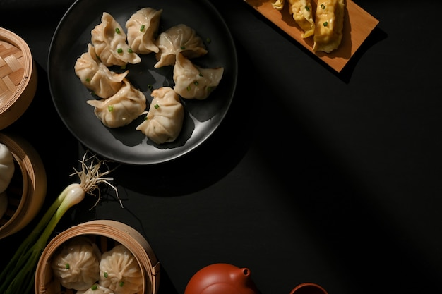 Top view of the table with dimsum dumplings, tea pot and copy space in restaurant