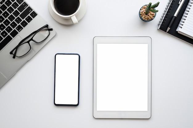 사무실에서 워크 벤치에 상위 뷰 태블릿 및 스마트 폰 빈 흰색 화면.