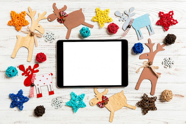 Top view of tablet on holiday wooden table. new year decorations and toys. christmas concept