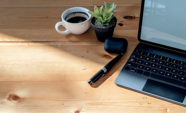コピースペースのある木製のトップテーブルにトップビューのタブレットキーボード、コーヒー、ペン、観葉植物