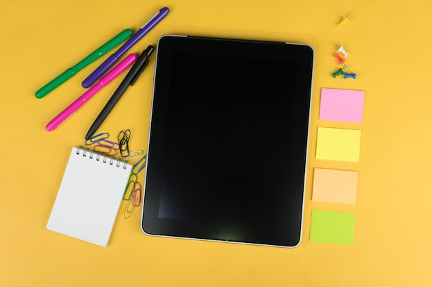 Top view of a tablet and school supplies like colored markers, sticker and clipers on yellow background, space for text.
