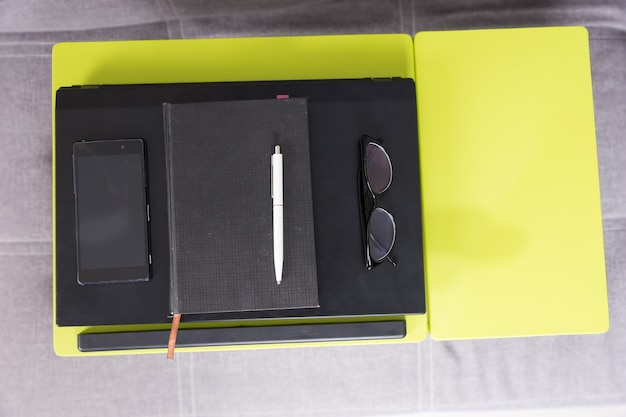 Top view of a tabletop workstation with closed laptop, a diary, glasses and mobile phone are arranged in strict order on it