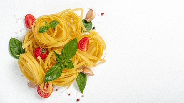 Top view of tagliatele pasta with basil and tomatoes with copy space