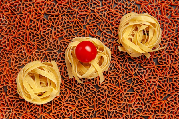 Top view tagliatelle on heart shaped italian pasta cherry tomato