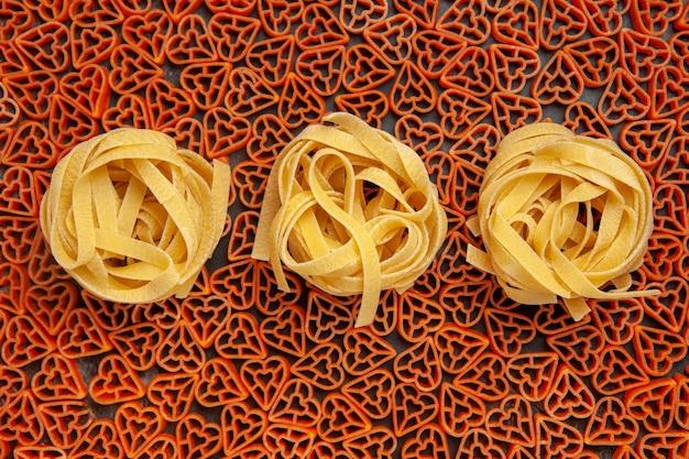 Top view tagliatelle on heart shaped italian pasta on dark table