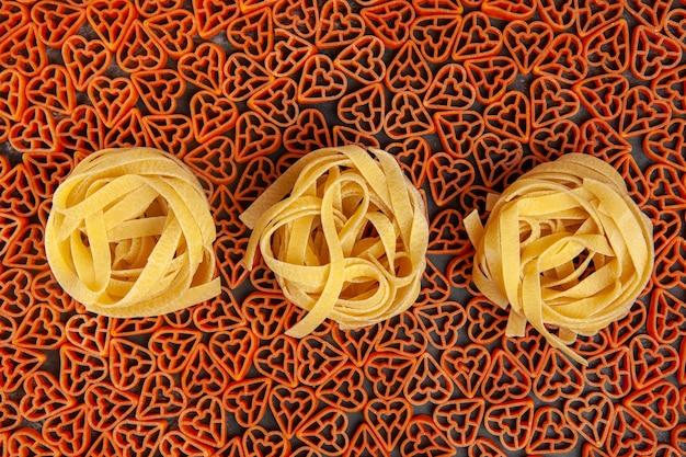 Top view tagliatelle on heart shaped italian pasta