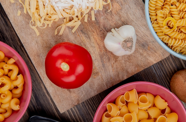 Top view of tagliatelle macaroni with flour garlic and tomato on cutting board with other types of pasta on wooden surface