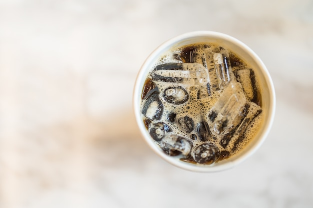 Top view of take away papercup of iced black coffee (americano) on table with copy space.
