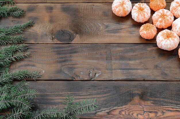 Top view tangeriens and pine branches on wooden background