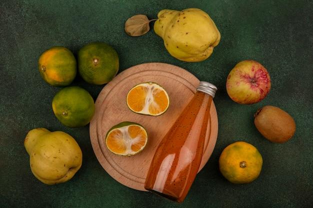 Vista dall'alto fette di mandarino su un supporto con pere mela kiwi e una bottiglia di succo di frutta