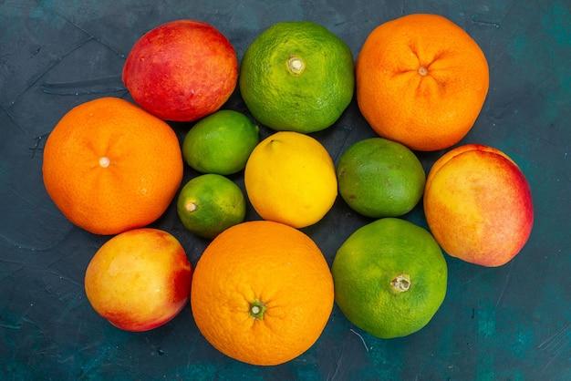짙은 파란색 책상 위의 귤과 복숭아 신선하고 부드러운 과일