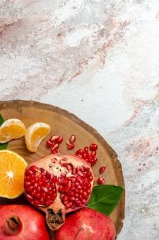 トップビューみかんとザクロ白い背景の上の新鮮なまろやかな果物果物の木の健康新鮮なビタミン食品
