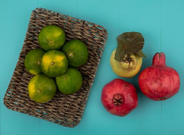 Merce nel carrello dei mandarini di vista superiore con i melograni e la pera