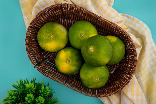 Mandarini di vista dall'alto in un canestro su un tovagliolo a quadretti giallo