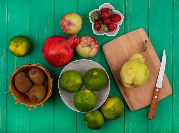 Mandarini di vista superiore nella ciotola con melograno e pera delle mele del kiwi sul tagliere