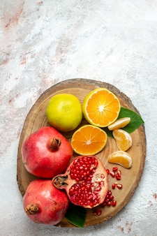 Top view tangerines and pomegranates fresh mellow fruits on white background fruit tree color health fresh