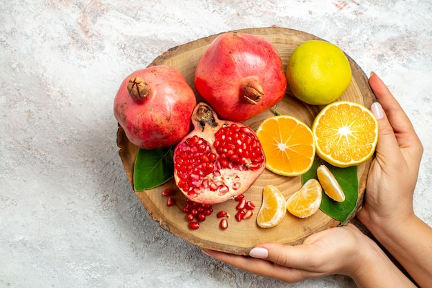 Top view tangerines and pomegranates fresh mellow fruits on a white background fruits tree health fresh vitamine food